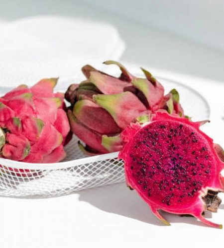 Fresh organic red dragon fruits on a white background, creative healthy food concept