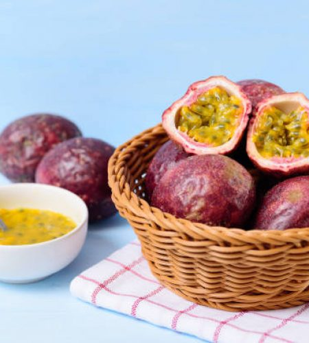 Fresh passion fruit in a basket and juice in a bowl